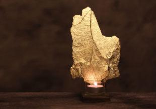Stück Schiefer mit echtem Blattgold veredelt auf einem Holz mit einem Teelicht